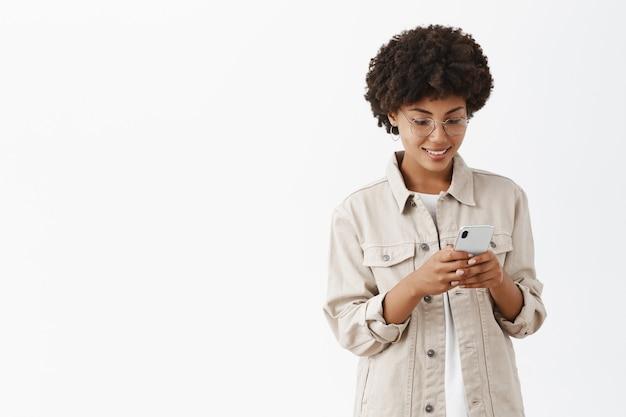 Toma interior de una encantadora mujer joven tranquila y feliz con gafas con peinado afro escribiendo un mensaje en un teléfono inteligente mirando con una sonrisa alegre en la pantalla del teléfono inteligente leyendo un artículo interesante en la web