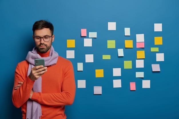 Toma interior de un estudiante serio que se prepara para el seminario, usa un dispositivo moderno, verifica el buzón de correo electrónico, lee noticias en internet, usa gafas, suéter con bufanda