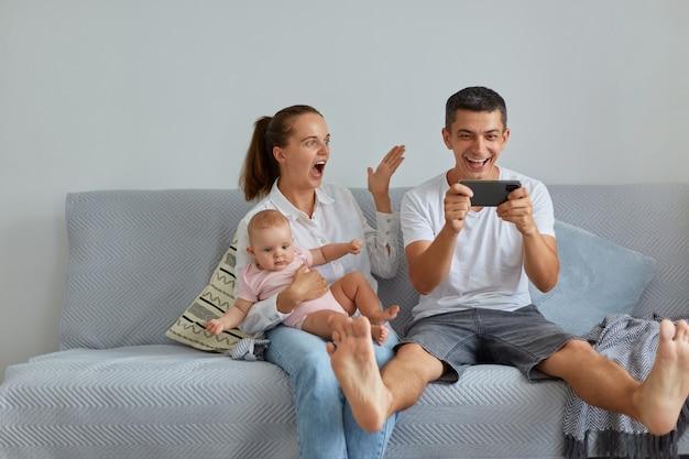 Toma interior de familia emocionada sentada en un sofá en la sala de estar, esposo sosteniendo el teléfono móvil en las manos, teniendo excelentes noticias sobre su victoria en la lotería, gente con infante gritando wow felizmente.