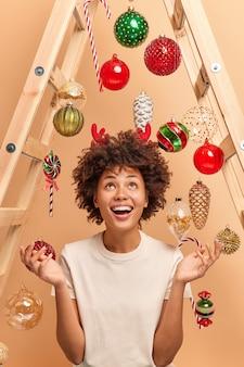 Toma interior de feliz mujer de piel oscura que mira con alegría por encima de las palmas de las manos y sonríe ampliamente usa cuernos de reno rojo usa escalera para decorar la casa para el año nuevo rodeada de juguetes navideños