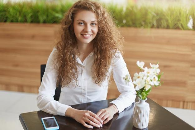 Toma interior de hermosa mujer joven con pelo largo y rizado
