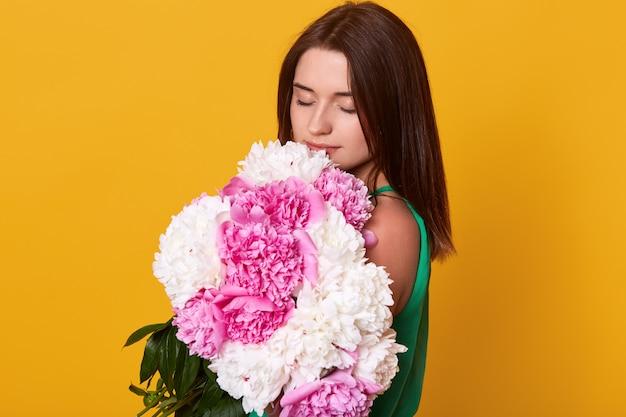 Toma interior de hermosa niña morena con ramo con peonías rosas y blancas