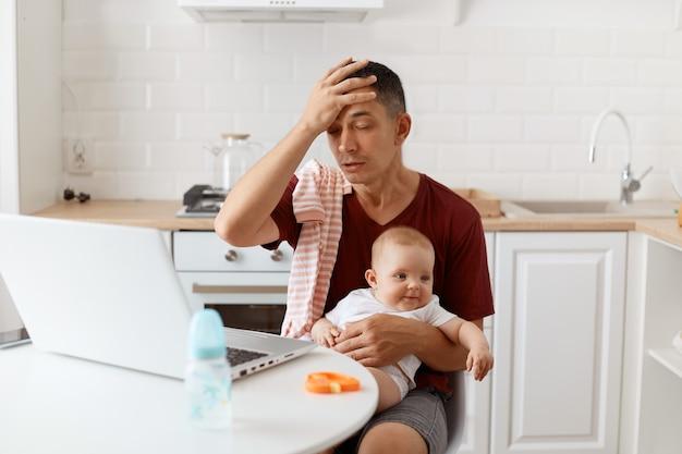 Toma interior de hombre autónomo guapo cansado con camiseta burdeos, posando en la cocina blanca, manteniendo la mano en la frente, siente dolor en la cabeza, sentado frente a la computadora portátil con el bebé en las manos.
