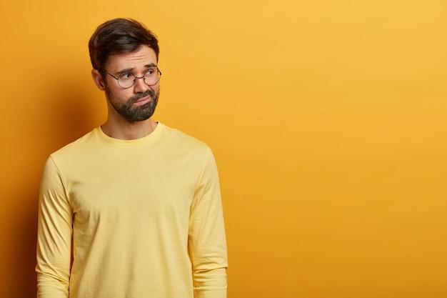 Toma interior de un joven barbudo pensativo frunce los labios y mira pensativamente en alguna parte, usa gafas redondas y un jersey amarillo, se para en el interior, un espacio en blanco adecuado para su contenido promocional