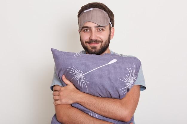 Toma interior de joven guapo parado sonriendo y abrazando la almohada, hombre posando en el dormitorio con los ojos vendados en la frente