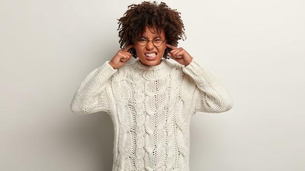 Toma interior de una mujer frustrada con piel oscura, cabello rizado, tapones para las orejas, aprieta los dientes, evita el mal sonido o el ruido, tiene una expresión insatisfecha, usa un jersey de punto blanco, aislado sobre una pared blanca