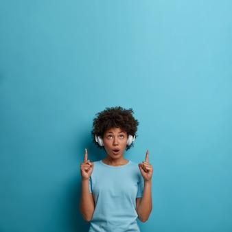 Toma interior de una mujer de piel oscura impresionada que usa auriculares en las orejas, se ve sorprendentemente arriba, indica un espacio en blanco, sorprendida con un anuncio impresionante, aislado en una pared azul. concepto de musica