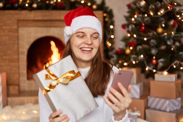Toma interior de una mujer sonriente feliz que tiene una videollamada o una transmisión en vivo y muestra una caja de regalo envuelta a la cámara del dispositivo, con gorro de papá noel, sentada en una habitación acogedora con decoración navideña.