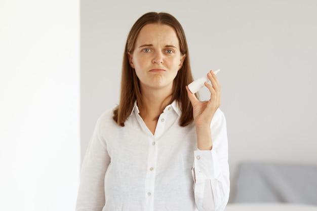 Toma interior de mujer triste confundida con enfermedad con camisa blanca de estilo casual, sosteniendo spray nasal en las manos y mirando directamente a la cámara con el ceño fruncido, siente gripe.