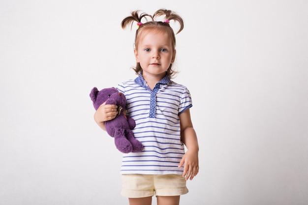 Toma interior de niño bonito en camiseta y pantalones cortos, tiene oso de peluche morado en las manos