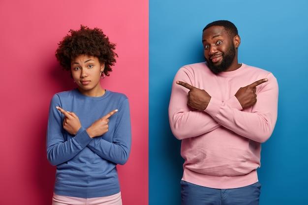 Toma interior de una pareja étnica confundida cruza las manos sobre el pecho, apunta a la izquierda y a la derecha, muestra las direcciones, no puede elegir