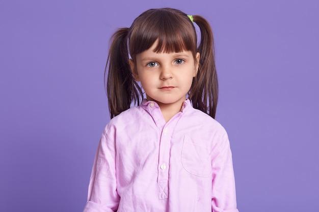 Toma interior de tranquila niña pequeña de pie contra el estudio de la lila
