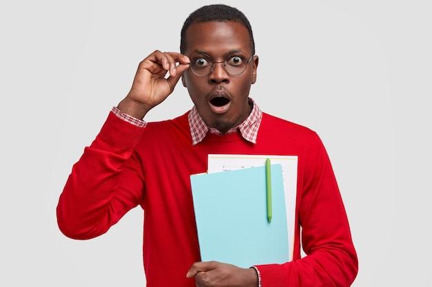 La toma en interiores de un chico de piel oscura estupefacto mantiene la mandíbula caída, usa ropa roja y gafas, lleva libros de texto, escribe un informe científico