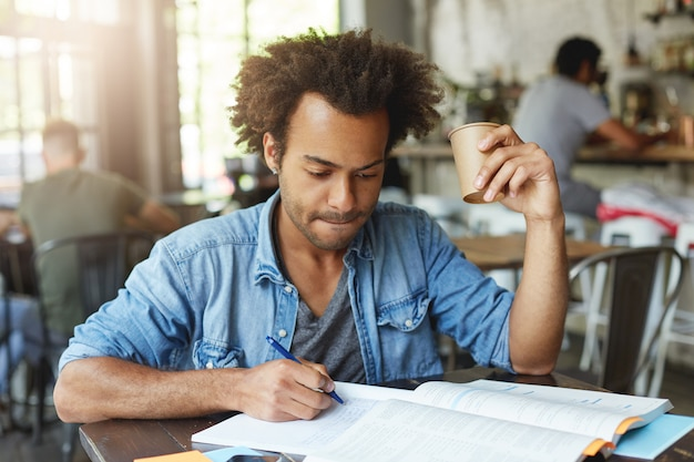 Toma en interiores de un estudiante negro guapo serio tomando café mientras trabaja en una tarea en casa, escribiendo en un cuaderno con un bolígrafo, mirando notas con expresión enfocada y persiguiendo los labios
