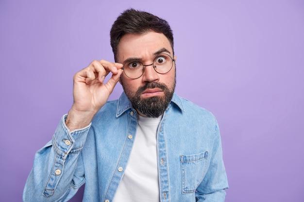 Toma en interiores de un hombre adulto sorprendido guapo con barba espesa que mira atentamente a través de gafas redondas vestido con camisa de mezclilla escucha noticias emocionantes quioscos sin palabras contra la pared púrpura
