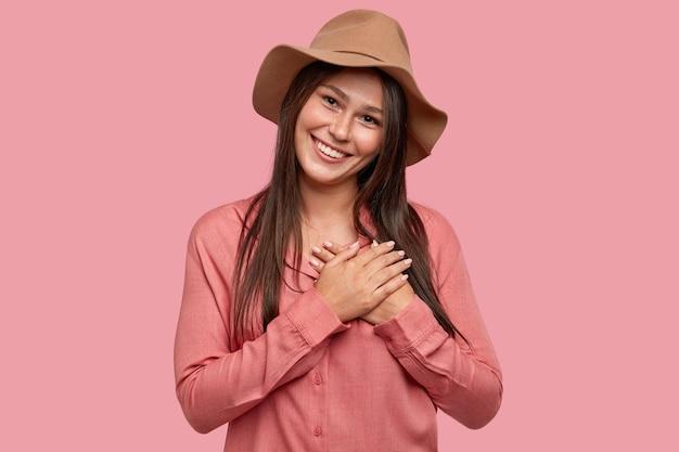 La toma en interiores de una mujer complacida y conmovida de aspecto agradable tiene una apariencia específica, mantiene ambas palmas en el corazón