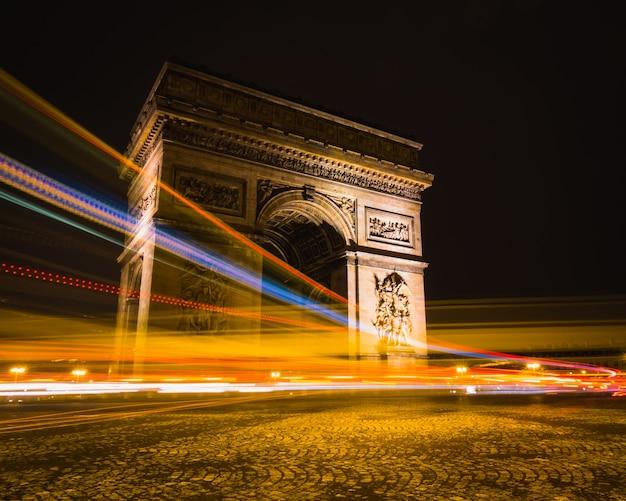 Toma de lapso de tiempo de senderos de luz alrededor del arco de triunfo en parís, francia.