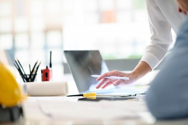 Toma de mano femenina con lápiz stylus y trabajando para un nuevo proyecto con su equipo en la oficina