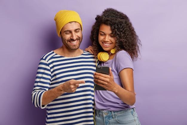 Toma de media longitud de la feliz novia y el novio que ven contenido de video divertido en el teléfono inteligente, párate cerca, tiene expresiones alegres, está conectado a internet inalámbrico
