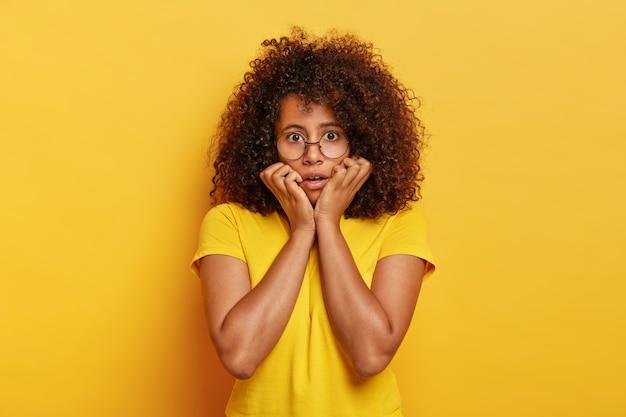 Toma de media longitud de una niña avergonzada con peinado afro, mira con miedo a la cámara, sostiene la barbilla, usa gafas ópticas y una camiseta amarilla brillante, posa en interiores