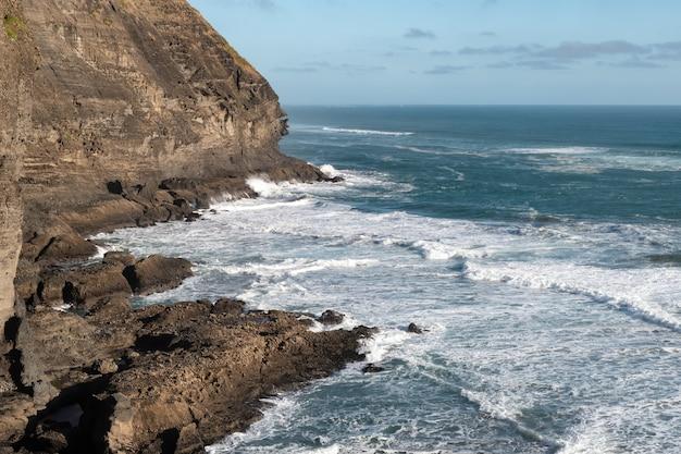 Toma de paisaje de una impresionante costa rocosa con acantilados y olas enojadas