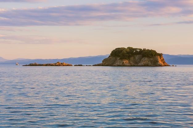 Toma panorámica de un acantilado sobre el cuerpo de un mar en calma bajo un cielo rosado