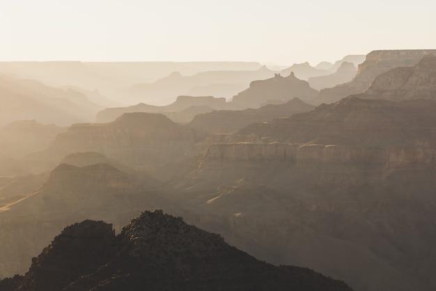 Toma panorámica borrosa de una colina con el fondo de altas montañas cubiertas de niebla