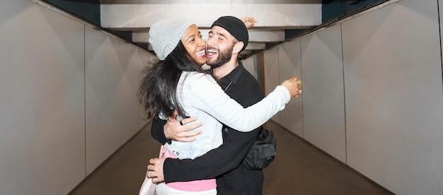 Toma panorámica -foto de estilo flash de vida- joven pareja interracial de amantes con máscaras faciales