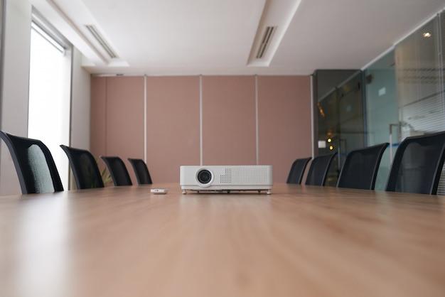 Toma panorámica de una oficina vacía con el proyector en medio de un escritorio de conferencia