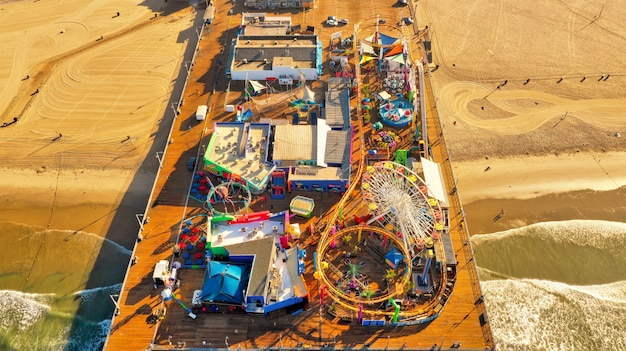 Toma panorámica de un parque de atracciones en un muelle de madera en la playa.