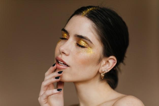 Toma de primer plano de alegre modelo femenino con cabello negro. retrato interior de mujer caucásica despreocupada tocando sus labios.
