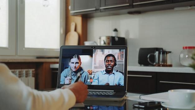 Toma de primer plano de colegas multirraciales que trabajan en cuarentena en casa haciendo una video llamada común por computadora