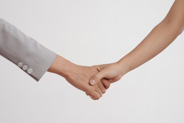 Toma de primer plano de dos mujeres irreconocibles dándose la mano en el estudio