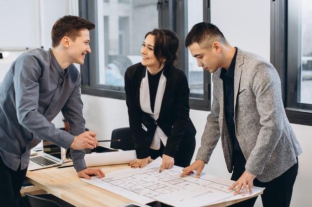 Toma de primer plano del grupo de arquitectos que dibujan el plan de construcción juntos en la oficina