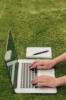 Toma de primer plano de manos humanas colocadas sobre la computadora portátil.