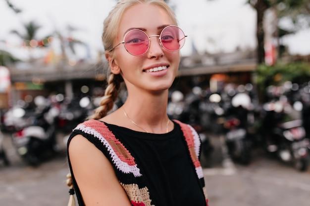 Toma de primer plano de mujer inspirada con trenzas rubias. modelo de mujer bronceada en gafas de sol rosas y traje de punto posando sobre fondo borroso.