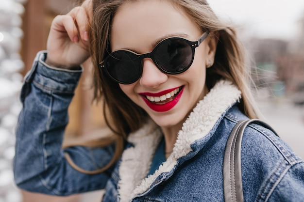 Toma de primer plano de la romántica chica caucásica posando con una hermosa sonrisa. retrato al aire libre de dama con cabello oscuro caminando por la ciudad en fin de semana de primavera.