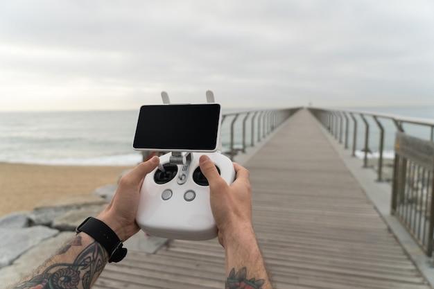 Toma de punto de vista de hipster y usuario milenario de nueva generación de nuevas tecnologías futuristas, usa el control remoto del dron para volar el dispositivo en el aire.