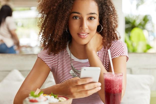Toma recortada de atractivo modelo femenino de raza mixta con peinado afro tupido actualiza el perfil en las redes sociales en el teléfono móvil, conectado a internet inalámbrico en la cafetería, cóctel de bebidas