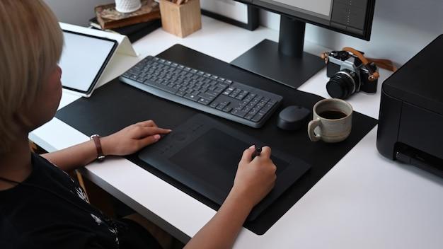 Toma recortada del diseñador gráfico que trabaja con tableta gráfica en la oficina moderna.