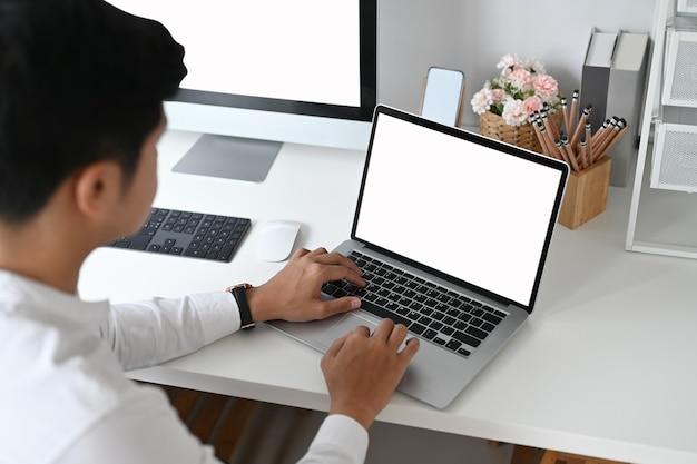 Toma recortada de diseño gráfico usando laptop y computadora en mesa blanca.