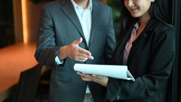 Toma recortada del gráfico de costos de análisis de trabajo en equipo de personas de negocios en la sala de reuniones.