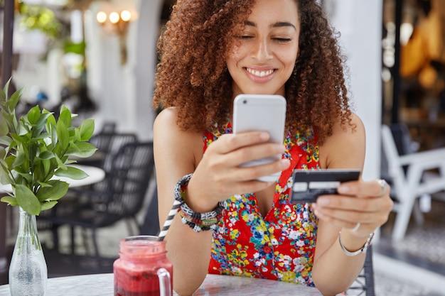 Toma recortada de hermosa mujer afroamericana con mirada feliz, tiene teléfono celular moderno y tarjeta de crédito, hace compras en línea