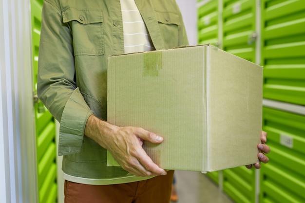 Toma recortada del hombre irreconocible que sostiene la caja de cartón de pie en las instalaciones de almacenamiento, espacio de copia