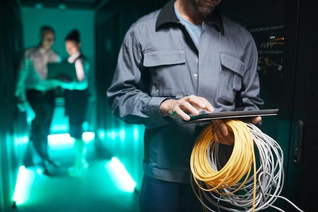 Toma recortada del ingeniero de redes con tableta digital en la sala de servidores durante el trabajo de mantenimiento en el centro de datos, espacio de copia