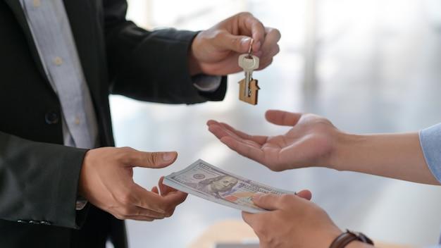 Toma recortada del intercambio de dólares y llaves de casa entre comprador y vendedor.