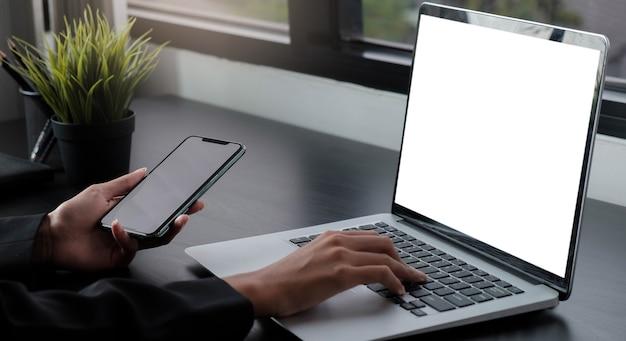 Toma recortada de la mano de la mujer de negocios mientras escribe en la tableta de la computadora con pantalla en blanco y sostiene el teléfono inteligente sentado junto a su colega