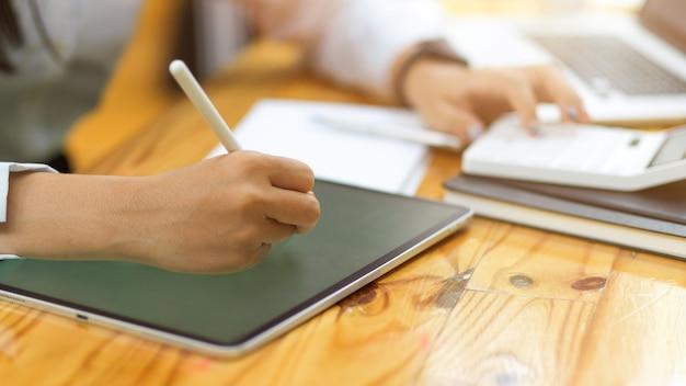 Toma recortada de manos femeninas con tableta y lápiz óptico mientras calcula en la mesa de madera