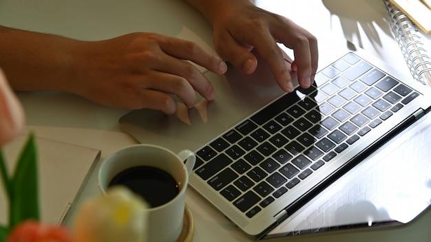 Toma recortada de manos masculinas trabajando con portátil