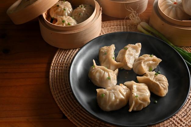 Toma recortada de la mesa de la cocina con un plato de albóndigas y vaporera de bambú